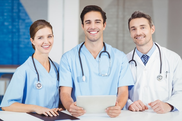 Portrait of smiling doctor and colleagues holding digital tablet
