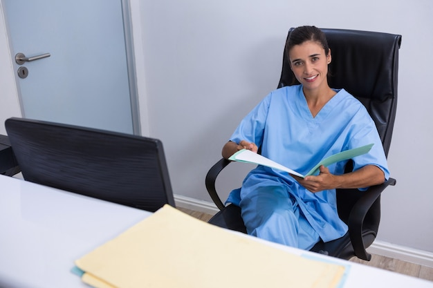 Portrait of smiling doctor holding file while sitting on chair
