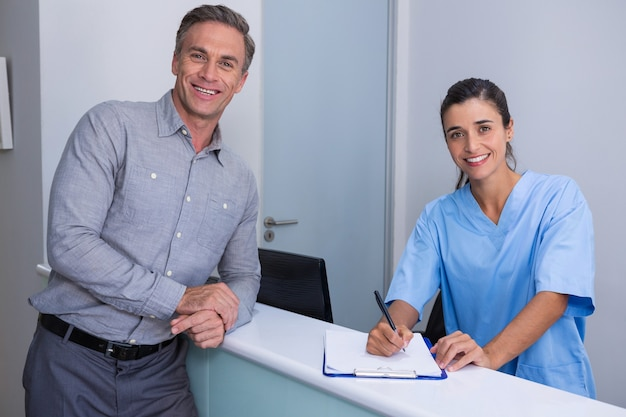 Portrait of smiling doctor holding pen standing by man at desk