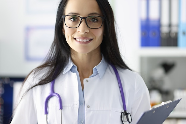 Portrait of smiling doctor with glasses in medical office. medical care and services concept