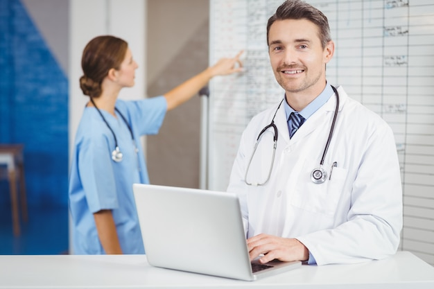 Portrait of smiling doctor working on laptop with colleague pointing at chart