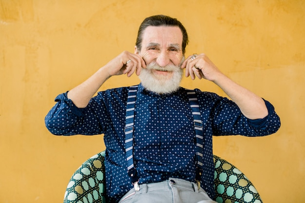 Portrait of smiling elderly bearded man in dark blue shirt and suspenders, posing isolated on yellow studio background, touching his mustache. people emotions and lifestyle concept.