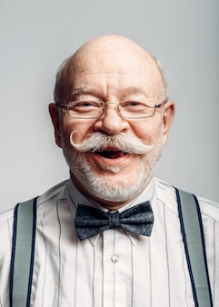 Portrait of smiling elderly man in a bow tie and glasses. mature senior