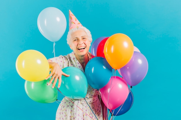 Portrait of a smiling elderly woman with colorful balloons on blue background