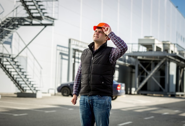 Portrait of smiling engineer in hardhat posing on construction site