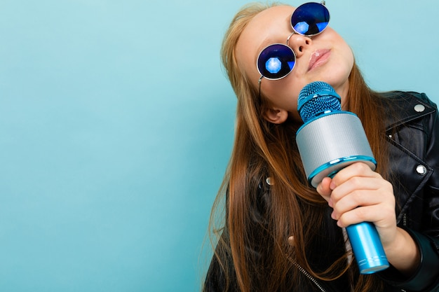 Portrait of a smiling european girl in sunglasses singing with a microphone on light blue wall