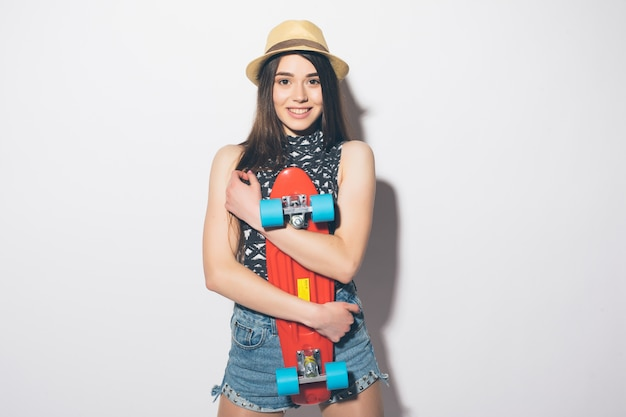 Portrait of a smiling excited woman holing skateboard isolated on the white wall