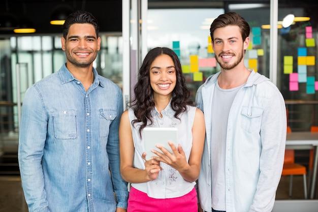 Portrait of smiling executives using digital tablet