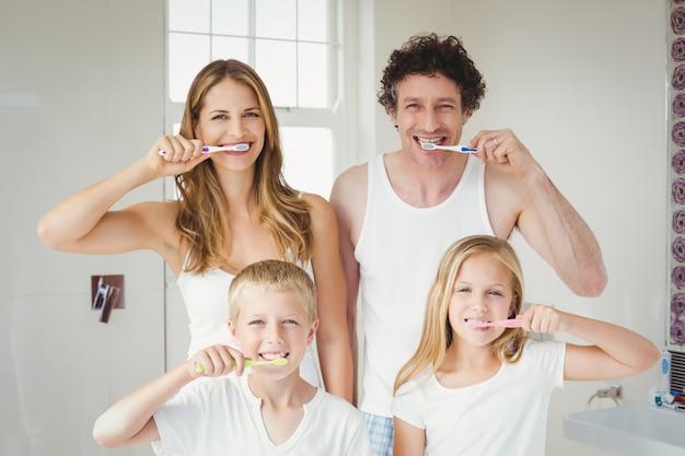 Portrait of smiling family brushing teeth