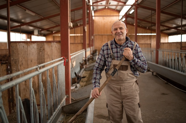 Portrait of smiling farmer or cattleman standing in farmhouse and feeding animals