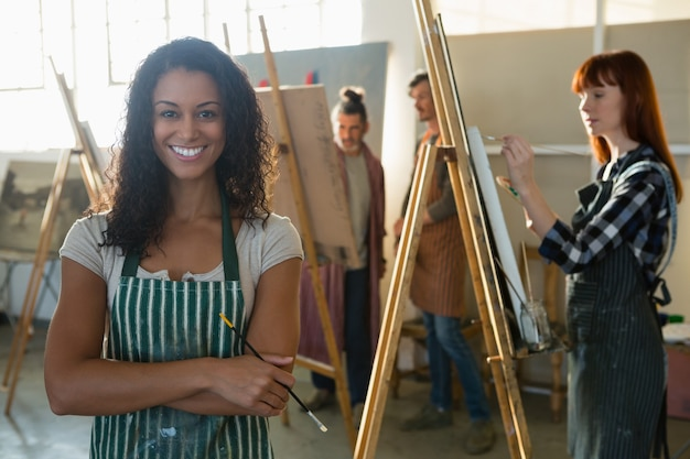 Portrait of smiling female artist with friends painting