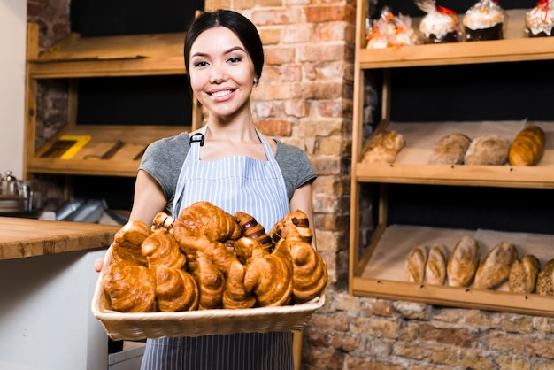 Portrait of a smiling female baker holding basket of baked croissant in bakery shop