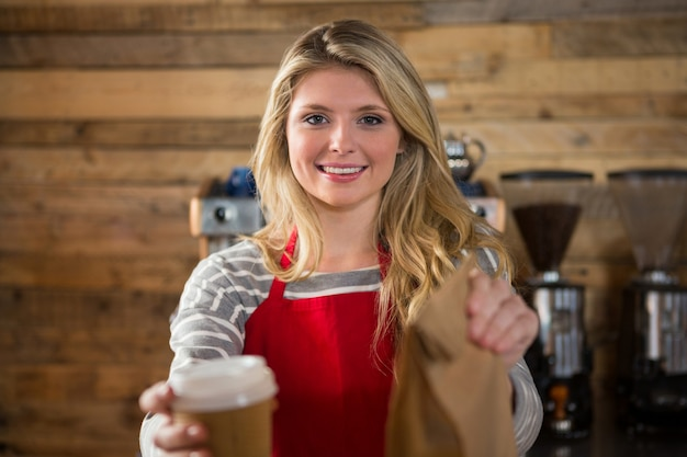 Portrait of smiling female barista holding coffee cup and paper bag in cafeteria