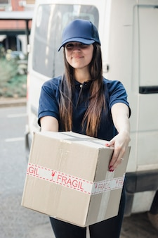 Portrait of a smiling female courier with cardboard box