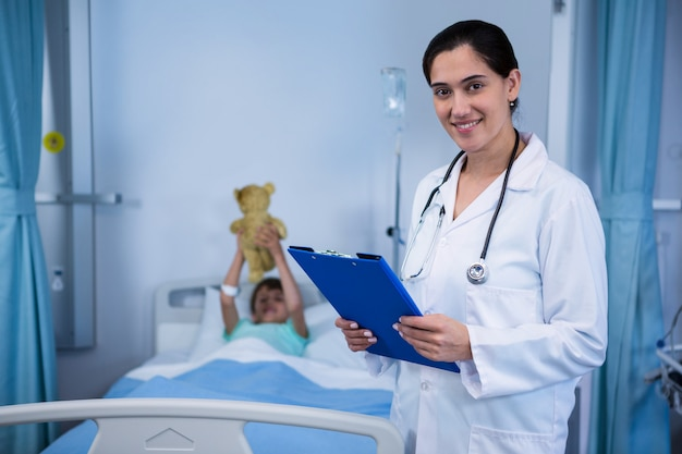 Portrait of smiling female doctor standing with clipboard in ward
