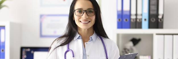 Portrait of smiling female doctor in white coat in medical office. medical centers concept