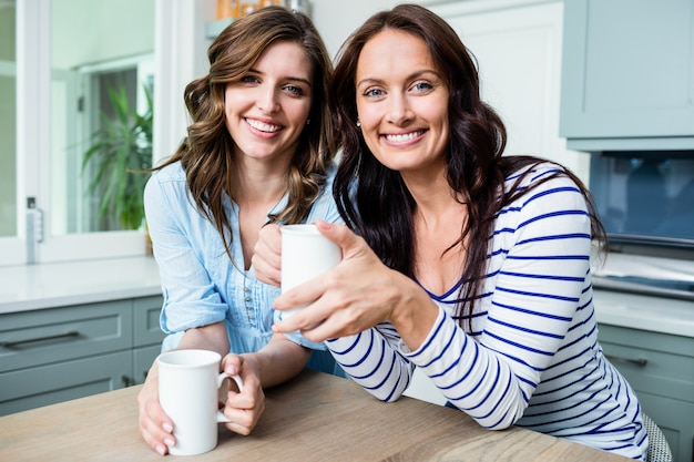 Portrait of smiling female friends holding coffee mugs while sitting at table