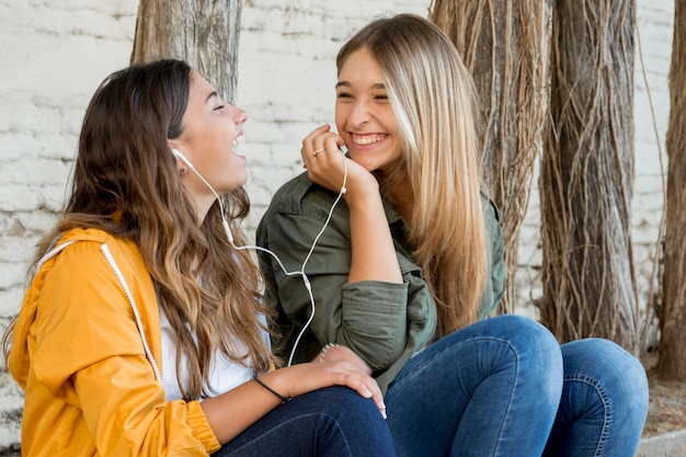 Portrait of smiling female friends sharing music