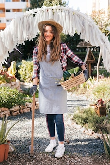 Portrait of a smiling female gardener in grey apron looking at camera