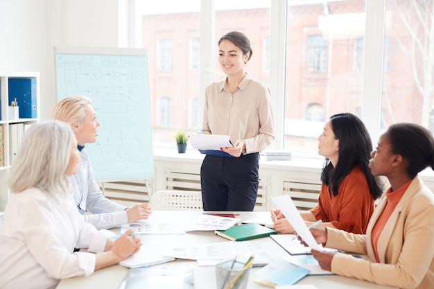 Portrait of smiling female manager presenting project plan to group of colleagues while standing by whiteboard during meeting in conference room