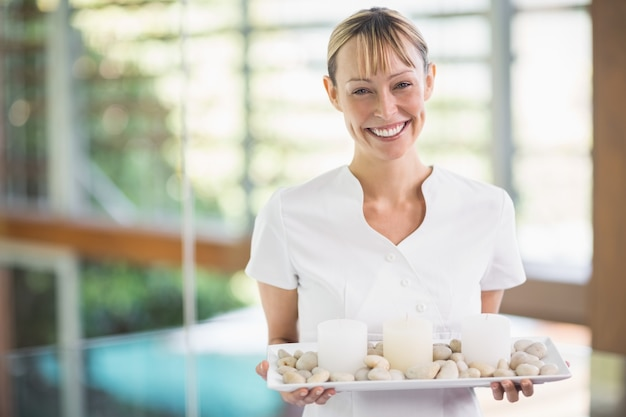 Portrait of smiling female masseur holding tray