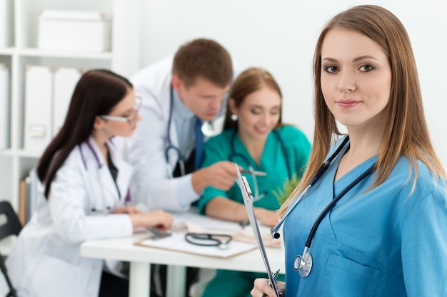 Portrait of smiling female medicine doctor holding folder with documents with her three colleagues working. healthcare and medicine concept.