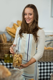 Portrait of smiling female staff holding a jar of cookies at counter