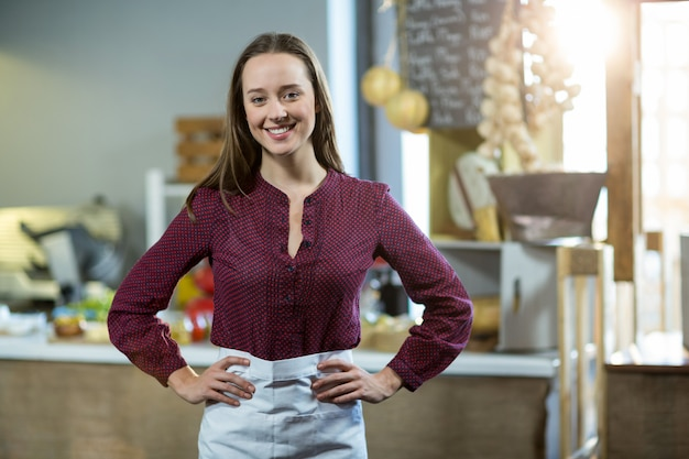 Portrait of smiling female staff standing with hands on hip against counter