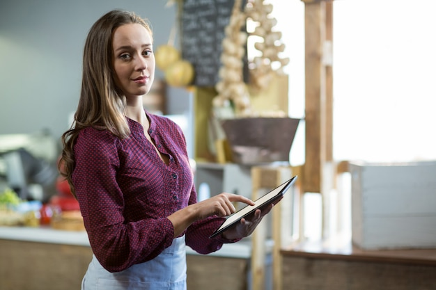 Portrait of smiling female staff using digital tablet at counter