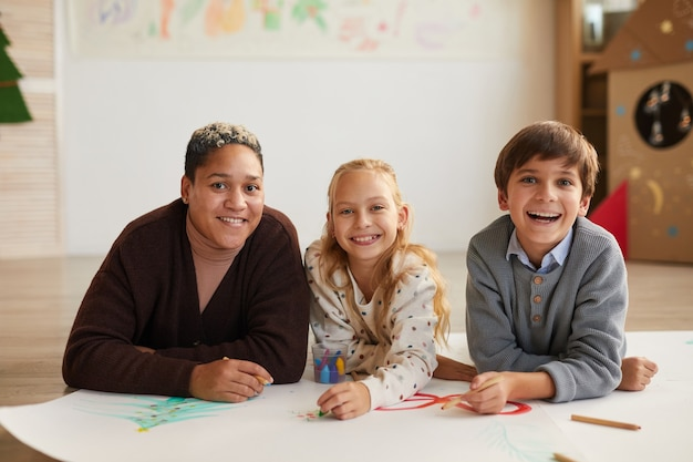 Portrait of smiling female teacher lying on floor and looking at camera with two kids drawing pictures while enjoying art class on christmas, copy space