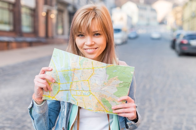 Portrait of a smiling female tourist standing on street showing map