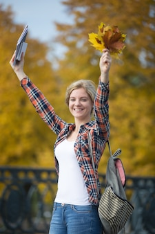 Portrait of smiling female young student outdoors holding yellow leaves
