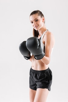 Portrait of a smiling fit sportswoman in boxing gloves