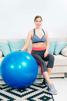 Portrait of smiling fit young woman sitting on sofa with large blue pilates ball in the living room