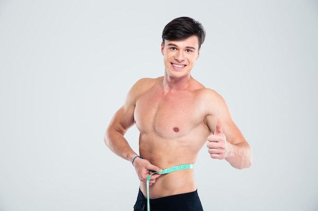 Portrait of a smiling fitness man measuring his body and showing thumb up isolated