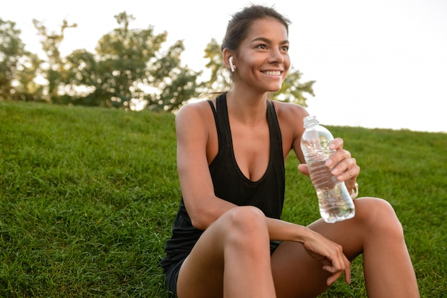 Portrait of a smiling fitness woman in earphones resting