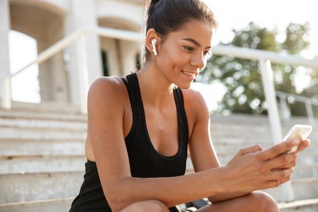 Portrait of a smiling fitness woman in earphones