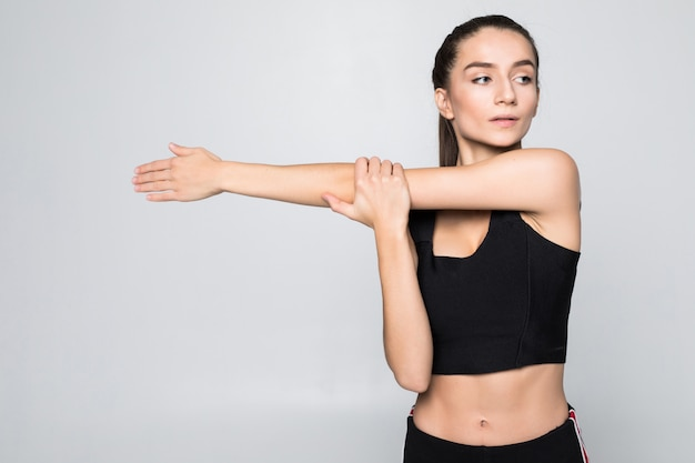 Portrait of a smiling fitness woman stretching her hands over white wall