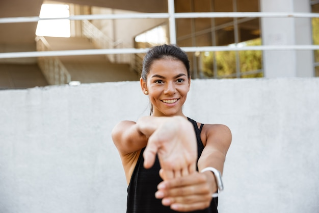 Portrait of a smiling fitness woman stretching her hands