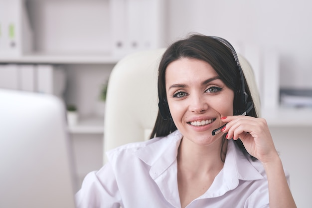 Portrait of smiling friendly helpdesk operator adjusting microphone headset while communicating with customer
