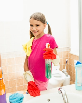 Portrait of smiling girl cleaning faucet and mirror at bathroom