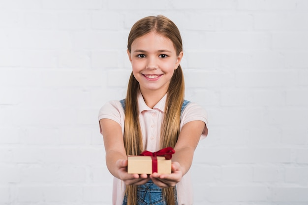 Portrait of a smiling girl giving wrapped present against white background