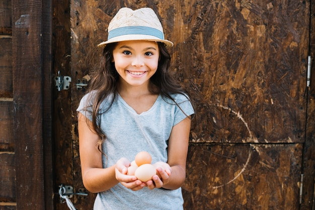 Portrait of a smiling girl holding eggs standing against rustic wall