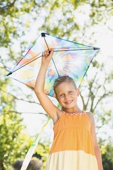 Portrait of smiling girl holding kite in park