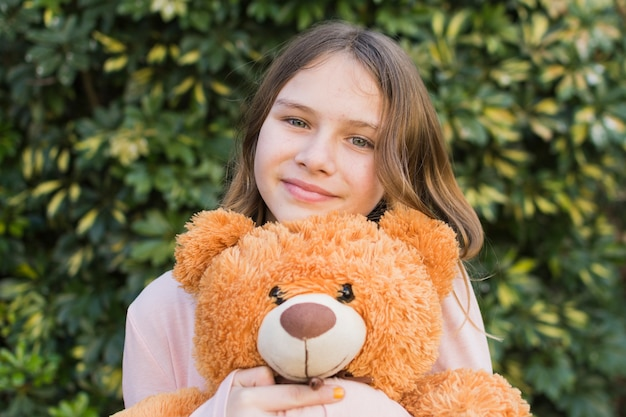 Portrait of a smiling girl holding teddy bear at outdoors