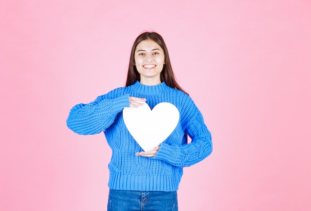 Portrait of smiling girl holding white heart isolated on pink.