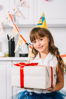 Portrait of a smiling girl holding white wrapped gift box tied with red ribbon on her birthday