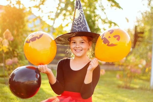 Портрет улыбающейся девушки в шляпе ведьмы с оранжевыми и черными воздушными шарами. забавный ребенок хеллоуина в костюме карнавала на открытом воздухе.