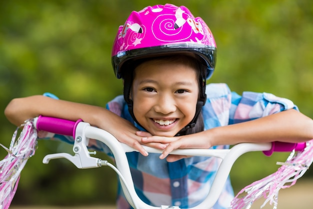 Portrait of smiling girl leaning on a bicycle