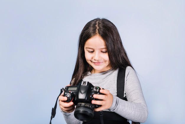Portrait of a smiling girl looking at camera against blue backdrop